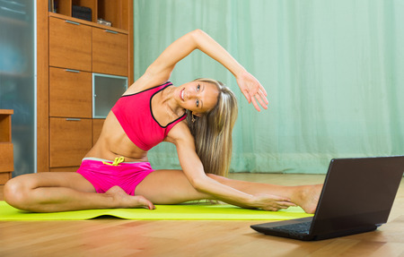 pilates: Young smiling woman having pilates class with notebook indoor