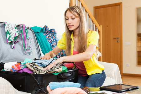 return trip: Attractive girl sitting near scattered clothes and packing suitcase