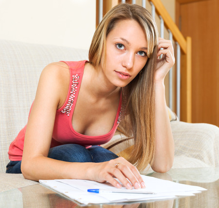 educational materials: Thoughtful student girl sitting on the sofa with educational materials in the hands Stock Photo