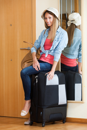Beautiful woman with handbag and trunk going on leave