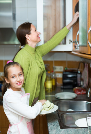 Smiling preschooler daughter helping mother washing dishes in the kitchen photo