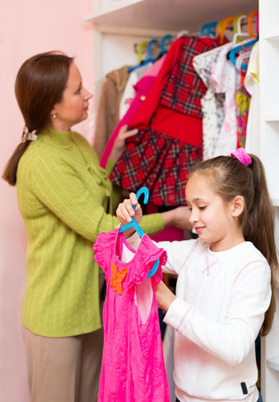 staying: woman and child staying near wardrobe with dresses on hangers.