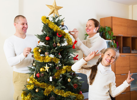 Smiling family of three preparing for Christmas in room at home. Focus on girl photo