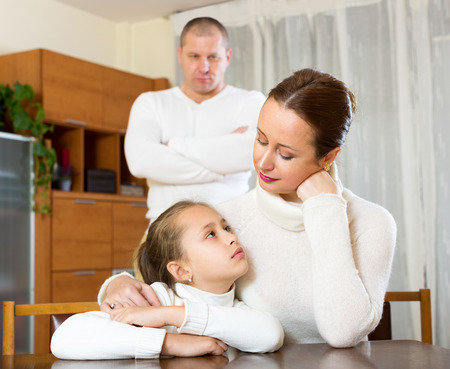 solace: small daughter gives solace to crying mother  at home and angry father