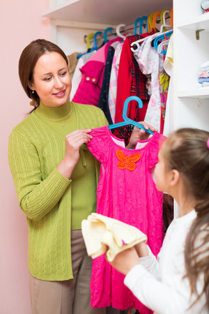 cloakroom: Preschooler girl with smiling mom choosing apparel in cloakroom