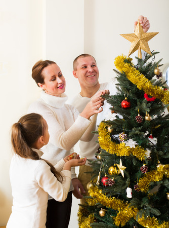 Parents and their child preparing for Christmas in living room photo