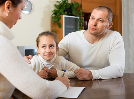 parsimony: Sad family with little daughter reading financial documents at home