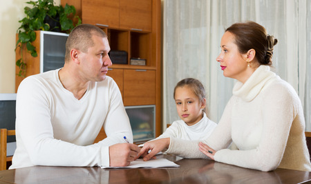 cupidity: Sad family of three with documents at home