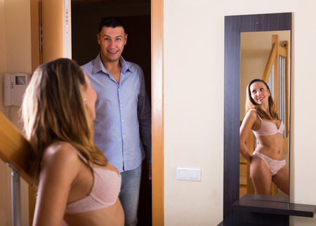 seducing: Young woman in underwear and boyfriend coming home Stock Photo