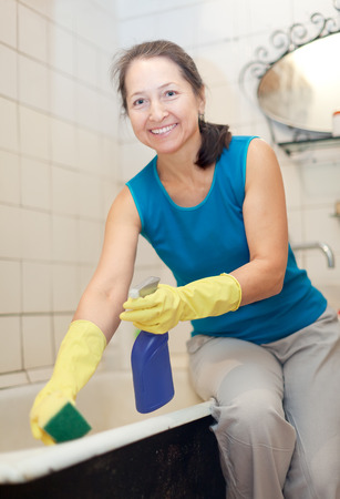 woman cleans bathroom with sponge and cleaner at her home photo