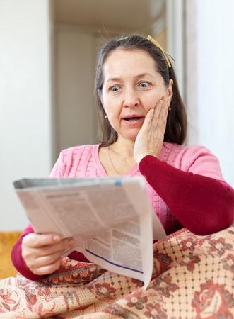 wonderment: wonder grief mature woman with newspaper Stock Photo