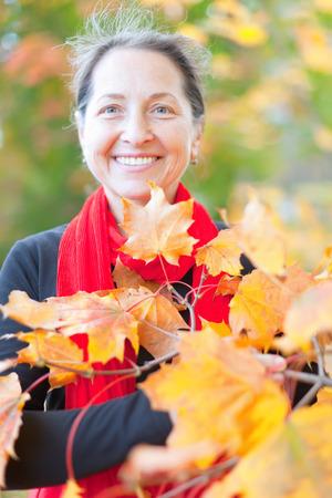 Portrait of happy mature woman  in autumn park photo