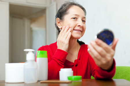 beautiful mature woman: mature woman looks to facial rhytid on face in mirror at home Stock Photo
