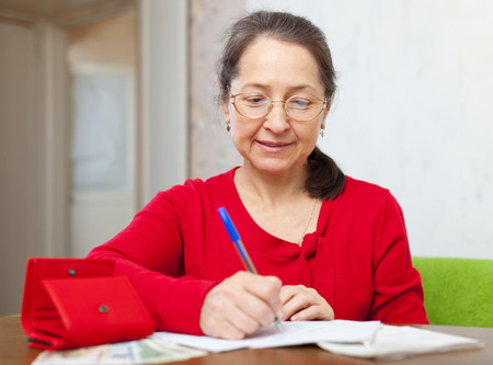 ruminate: serious mature woman with bill and money at her home Stock Photo