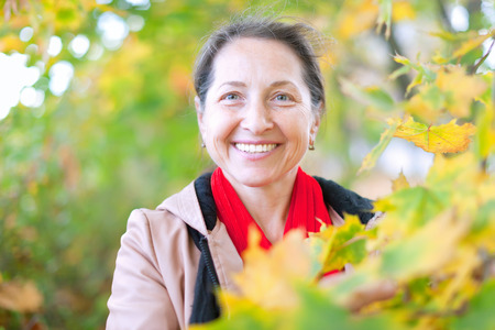 45 50 years: Portrait of happy mature woman  in autumn park Stock Photo