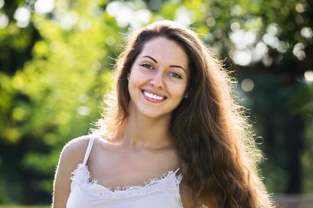 mujer alegre: Retrato al aire libre de la mujer sonriente de pelo largo