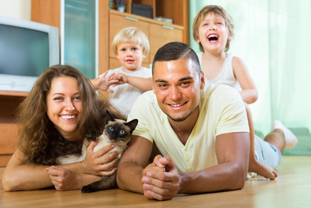 Happy smiling young family of four laying on the floor in living room with kitten. Focus on man photo