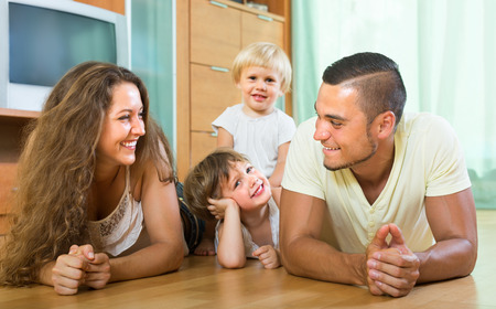 gladful: Happy smiling young parents and two children having fun at home Stock Photo