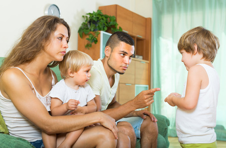berate: Young parents scolding little daughter at home. Focus on little girl