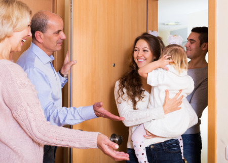 welcome home: happy young family with two daughters visiting grand parents