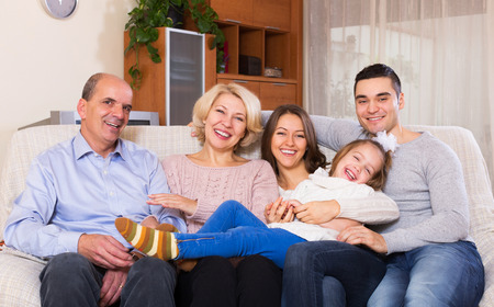 grand father: Long family with grand children posing indoors Stock Photo