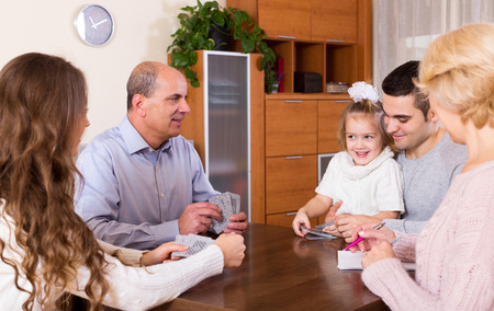 Portrait of smiling multigenerational family playing cards photo