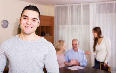 hypothec: smiling guy and big family with agent at distance indoor today Stock Photo