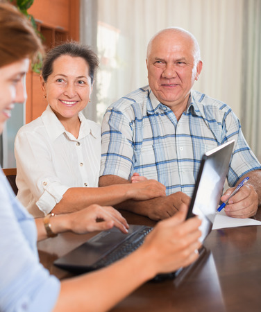 outreach: Mature couple answer questions of outreach worker with notebook in home