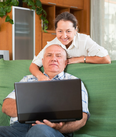 Happy pensioner with laptop  at table in home photo