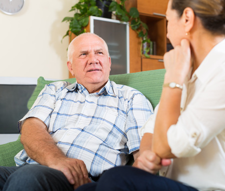 old home: mature family having serious talking in home interior