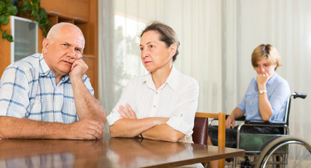 incapacitated: Tired mature couple and disabled person on chair indoor
