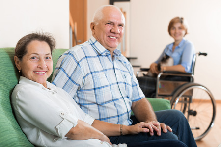 Happy mature couple and  daughter in wheelchair
