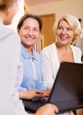 55 60: Insurance agent consulting happy female pensioners at home