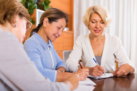 55 60: Cheerful mature female pensioners making list and smiling indoor. Focus on brunette female Stock Photo