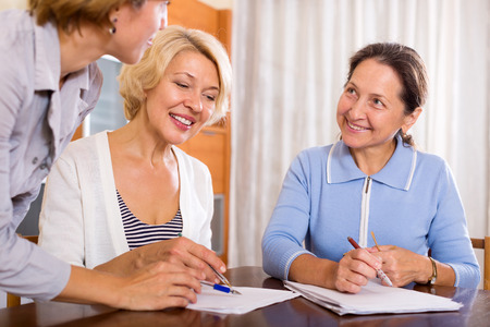 Smiling mature women consulting at insurance agent office. Focus on the left woman photo
