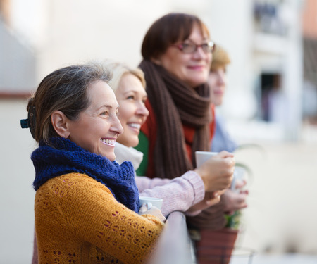 old ladies: Smiling elderly female in warm clothes having cup of hot tea on terrace. Focus on brunette woman