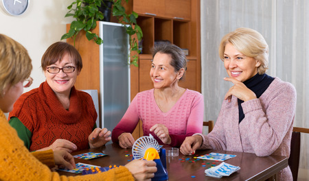 55 60: Happy senior female friends having fun with table game indoor