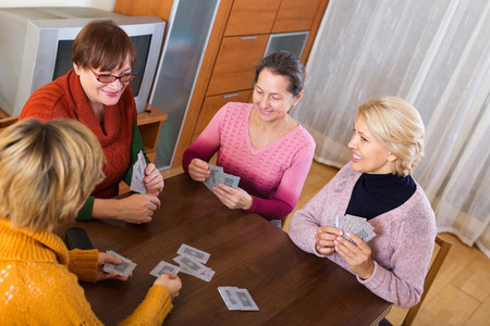 Mature female having fun with pack of cards indoor photo