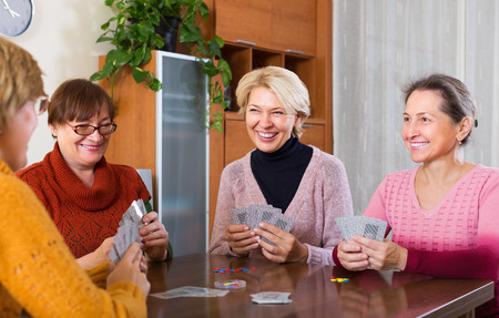 55 60: Happy elderly women having fun with pack of cards indoor Stock Photo