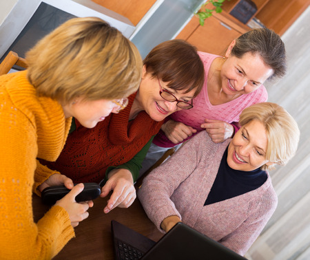 55 60: Happy female pensioner friends studying laptop  at home Stock Photo