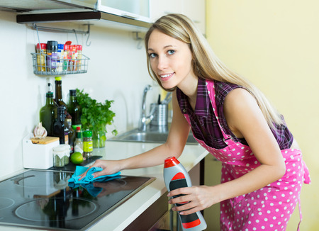 cleaning kitchen: Smiling blonde girl cleaning electric panel with rag and cleanser