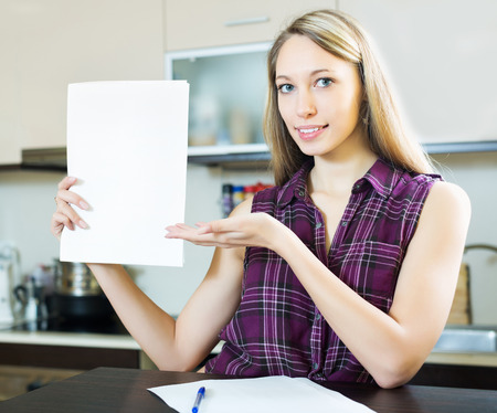 calculated: Happy girl with papers at home kitchen