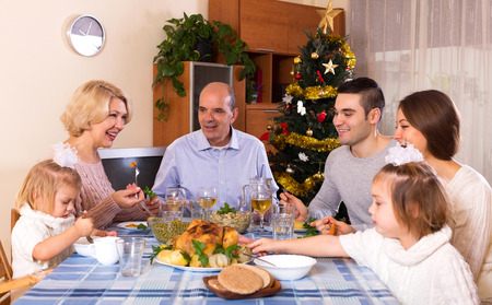 60 65 years: happy parents with adult kids and grandchildren celebrating xmas