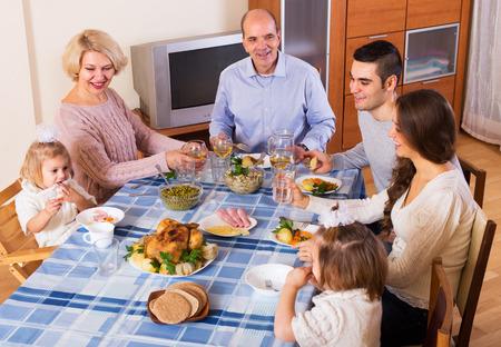 conversaciones: Familia multigeneracional sentado a la mesa para la cena y las conversaciones