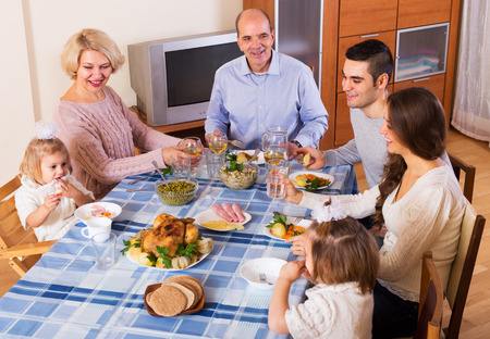 talks: Multigenerational family sitting at the table set for dinner and talks Stock Photo