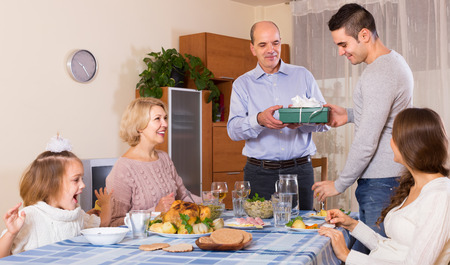 congratulating: Happy people congratulating heartily family member at home