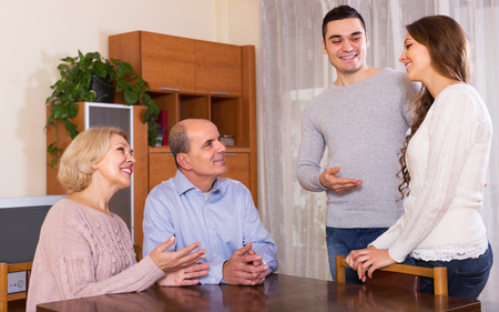 affiance: Happy young man showing his future wife to smiling parents