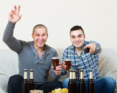 Two excited men drinking beer and watching football game indoor. Focus on one Stock Photo