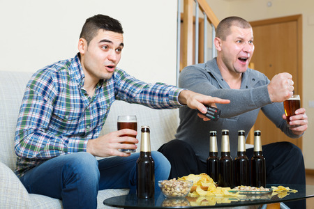 commenting: Adult happy friends sitting at table with beer and commenting sport tv channel