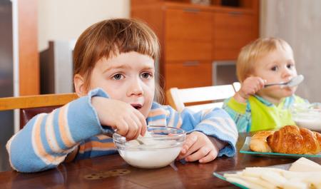 2 to 3 years: bambini a mangiare la prima colazione da latte a tavola Archivio Fotografico
